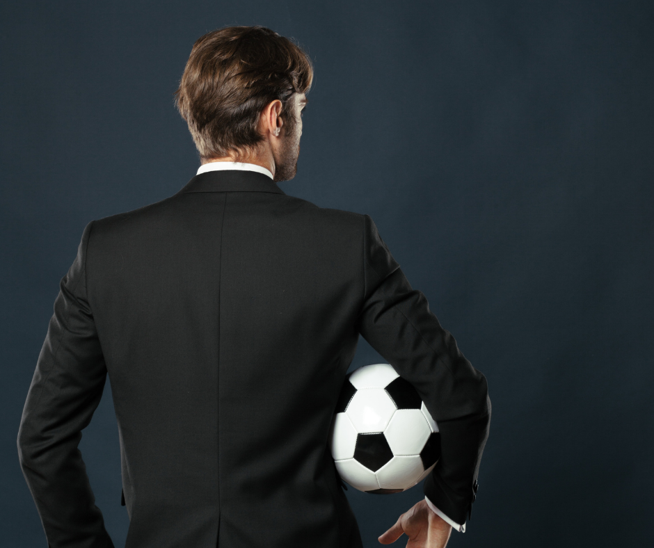 A man in a suit holding a football, standing with authority like Pep Guardiola